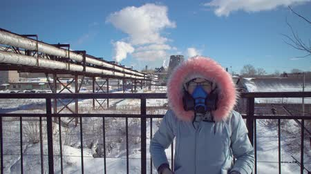 metallurgical plant : Portrait of a young woman in a protective mask and gray park against the background of the pipes of the metallurgical plant on a winter day.