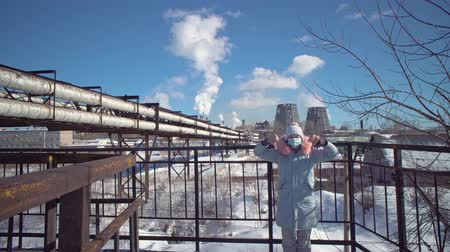 výfuk : Portrait of a young woman in a protective mask and gray park against the background of the pipes of the metallurgical plant on a winter day. Young woman showing thumbs down.