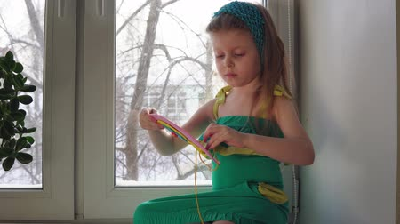 závit : Cute little girl sews a handbag. The child learns to use a needle and thread sitting on the windowsill on the background of snowy trees, dolly shot.
