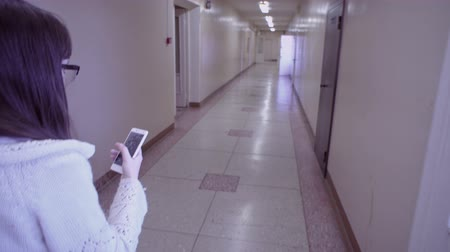 pletený : A young woman in a white knitted jacket is talking on the phone during a break and walking down the corridor in an old building.View of the hallway over the female shoulder.