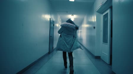 ondergronds : A young woman in a panic runs away from her pursuer along a dark corridor. The girl pulls a phone out of her parka pocket and tries to call for help. A sign with Russian text above the doors: exit.