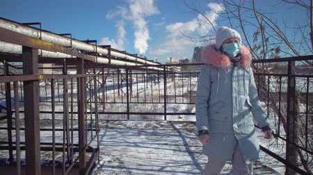 goes : A young woman in a protective mask and gray park goes over the bridge against the background of the pipes of a metallurgical plant on a winter day.