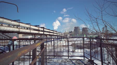 węgiel : A young woman in a protective mask and gray park goes over the bridge against the background of the pipes of a metallurgical plant on a winter day.