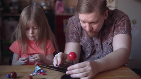 education kids : Little cute girl and young man model the layout of the solar system. Father helps his daughter to create a scientific project.