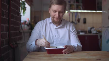 kluski : Hungry adult businessman with thick red beard and mustache eats Instant noodle with chopsticks.