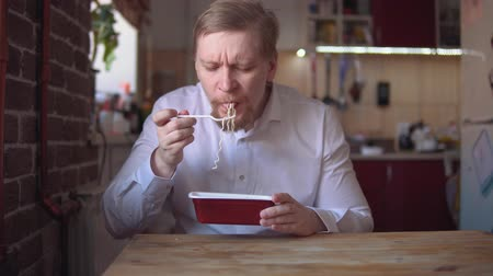 kluski : Hungry adult businessman with thick red beard and mustache eats Instant noodle with fork.