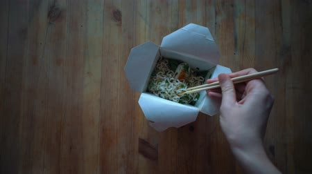 ramen : Top view, female hands with chopsticks pick up instant noodles from a paper box on a wooden table. The concept of fast food and semi-finished products, fast food houses.