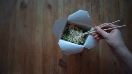 лапши : Top view of hand with chopsticks mixes instant noodles and hot water in a paper bowl, dolly shot.The concept of fast food and semi-finished products, fast food houses.