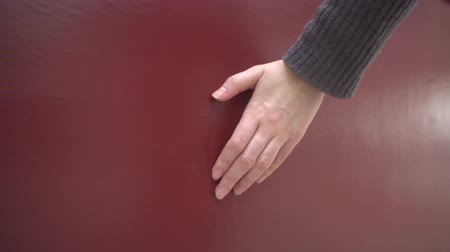sıva : A woman walks next to a smooth red wall and touches her flat surface with her hand.