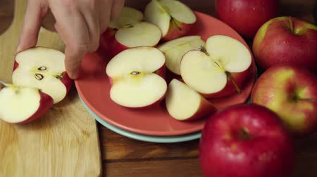 houthakken : Closeup of a man cuts a red apple into halves and quarters with a knife. Ripe juicy fruit cut into pieces on a chopping wooden board,dolly shot. Stockvideo