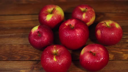 nesnelerin grubu : Many red, wet, mouth-watering apples lie on a wooden table, the camera slowly turns around the fruit.