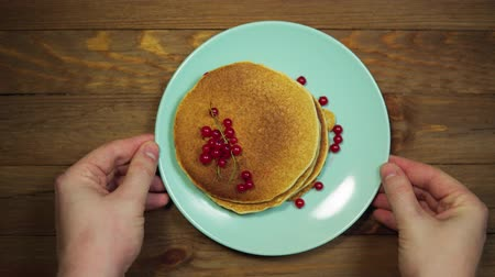 оладья : Top view of a hand putting a plate with appetizing pancakes and red currants on a wooden table, the camera is moving from left to right.