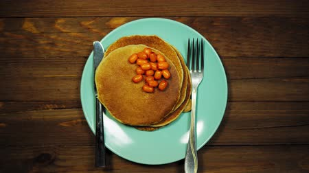 оладья : Top view hands put a plate with pancakes and berries on a wooden table, dolly shot.