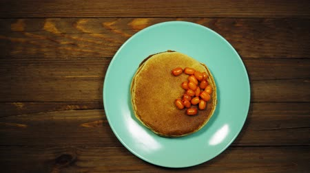 красная смородина : Top view on azure plate with appetizing pancakes and orange sea-buckthorn berries on a wooden table, the camera moves from left to right.