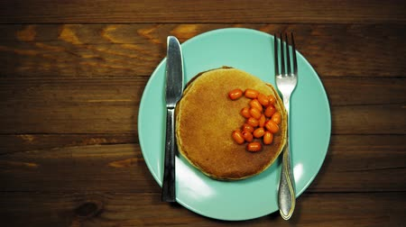 buckthorn : Top view on azure plate with appetizing pancakes and orange sea-buckthorn berries on a wooden table, the camera moves from left to right.