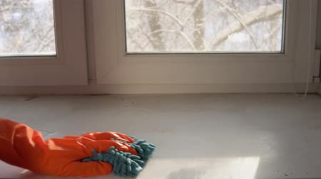 prát : A hand in an orange protective glove with a blue damp rag washes and cleans the window sill from dust and dirt. The human wipes the sill to reduce allergens and give freshness to the room. Dostupné videozáznamy