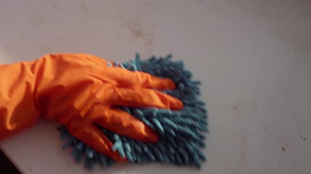 mopping : A hand in an orange protective glove with a blue rag washes and cleans the window sill from dust and dirt. The human wipes the sill to reduce allergens and give freshness to the room, view from above.