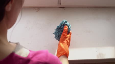 sıkıcı iş : A hand in an orange protective glove with a blue damp rag washes and cleans the window sill from dust and dirt, a look over the shoulder of a woman.