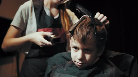 grzebień : Close-up of a hairdresser doing a hair-dressing machine for a boy. Haircut of a childrens hair trimmer and comb at the hairdresser.