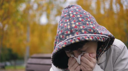 tosse : A young sick woman sneezes and blows her nose against the background of yellow foliage in the city park in Indian summer.