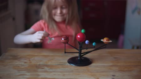 cıva : Child plays with the layout of the solar system. Little blonde girl flying silver toy rocket through planets. The kid presents himself as a spacecraft pilot. Stok Video