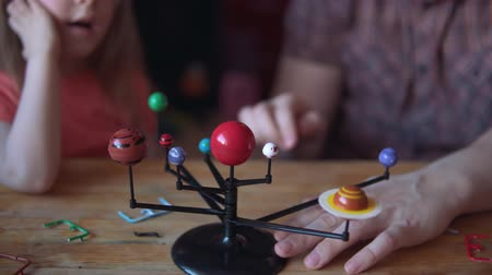 sich vorstellen : Little cute girl and young man model the layout of the solar system. Father helps his daughter to create a scientific project.