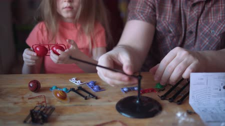 mercúrio : Little cute girl and young man model the layout of the solar system. Father helps his daughter to create a scientific project.