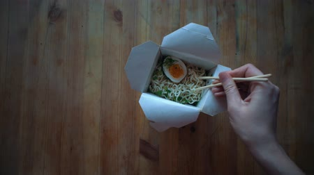 conveniência : Top view, female hands with chopsticks pick up instant noodles from a paper box on a wooden table. The concept of fast food and semi-finished products, fast food houses.