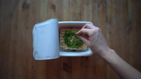 kluski : Top view of cooking instant noodles, female hands pours pieces green onion into cup with instant noodles on wooden table. Greenery lies in the shape of a heart. Wideo