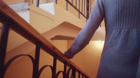 percepção : A woman comes down the stairs, a female hand touches varnished smooth wooden railing.