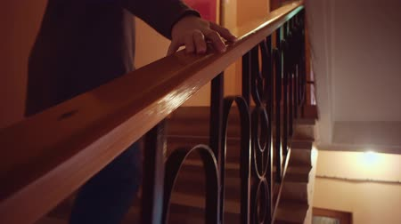 percepção : A woman walks upstairs, a female hand touches varnished smooth wooden railing. Stock Footage
