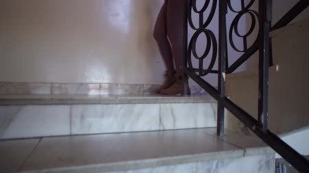бежевый : A girl in beige leggings and brown shoes goes down the marble steps down to the indoors. The stone staircase is decorated with metal black railing. Стоковые видеозаписи