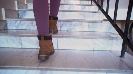 lépcsőház : A young woman in beige leggings and brown boots climbs the marble steps to the indoors. The stone staircase is decorated with metal black railing. Stock mozgókép