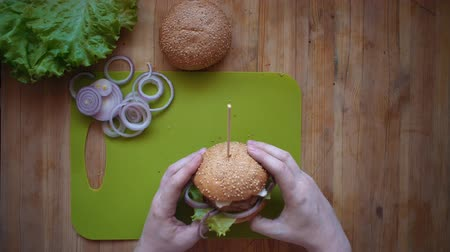 houska : Flat lay of the process of cooking a burger overhead view the wooden table with ingredients and male hands. A man checks a hamburger, twists a sandwich, is going to eat it.