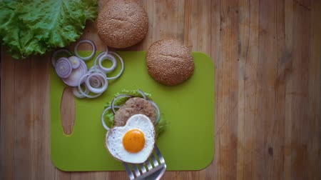 houska : Flat lay of the process of cooking a burger overhead view the wooden table with ingredients and male hands.Male hands put a heart-shaped fried egg on a hot cutlet and bun