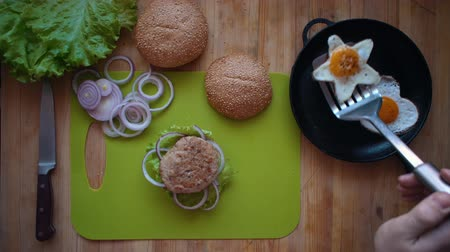 egg laying : Flat lay of the process of cooking a burger overhead view the wooden table with ingredients and male hands. Male hands put a star-shaped fried egg on a hot cutlet and bun. Stock Footage