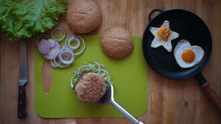кунжут : Top view of the process of cooking a burger right above the wooden table. Male hands put a hot cutlet on a red onion, green salad and bun.