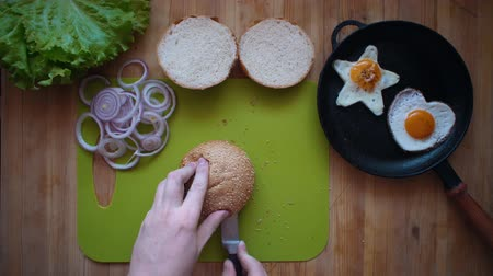 bread pan : Top view of the process of cooking a burger right above the wooden table. Male hands cut a bun in half with a kitchen knife. Stock Footage