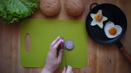 houska : Top view of the process of cooking a burger right above the wooden table. A man cuts red onions with rings with a kitchen knife. Dostupné videozáznamy