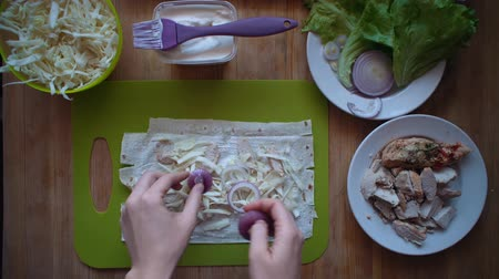 chawarma : Womens hands spread red onions on boiled chicken, cabbage and thin pita. Flat lay of the process of cooking a shawarma overhead view the wooden table with ingredients and female hands. Stock Footage