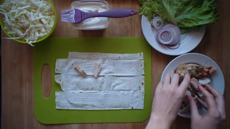 chawarma : Flat lay of the process of cooking a shawarma overhead view the wooden table with ingredients and female hands. Womens hands spread boiled chicken on thin pita. Stock Footage