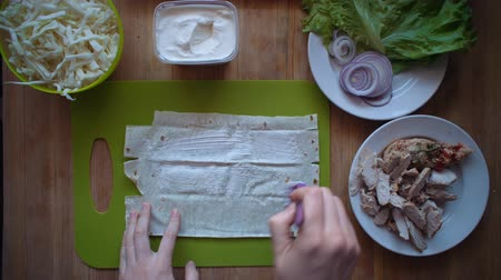 pita : Flat lay of the process of cooking a shawarma overhead view the wooden table with ingredients and female hands. Human puts sauce on pita bread with a cooking brush. Stock Footage