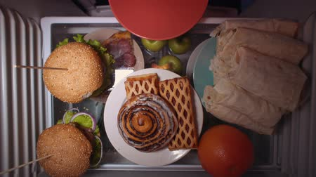 дверь : Top view on the shelf of the refrigerator. Someone puts sweet pastries on a plate. Irregular nutrition and sleep disturbance.