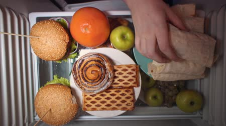 полночь : Top view on the shelf of the refrigerator, someone chooses between fruit and pastries and takes shawarma. Irregular nutrition and sleep disturbance.