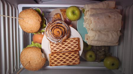 shoarma : Top view on the shelf of the refrigerator the problem of choosing between healthy and unhealthy food someone takes a green apple instead of shawarma at night. Irregular nutrition and sleep disturbance Stockvideo