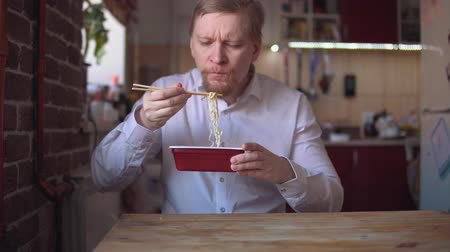 kluski : Hungry adult businessman with thick red beard and mustache eats Instant noodle with chopsticks