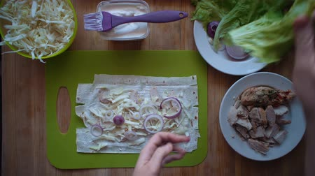 lavash : Flat lay of the process of cooking a shawarma overhead view the wooden table with ingredients and female hands. Womens hands spread boiled chicken on thin pita. Stock Footage