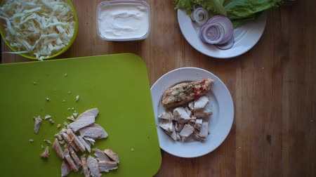 repolho : Flat lay of the process of cooking a shawarma overhead view the wooden table with ingredients and female hands. Womens hands poured into a plate of pieces of boiled chicken.