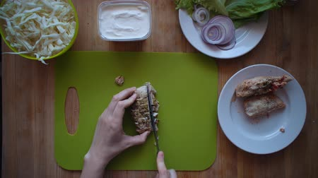 göğüs : Flat lay of the process of cooking a shawarma overhead view the wooden table with ingredients and female hands. Womens hands are cutting a boiled chicken breast with a knife.