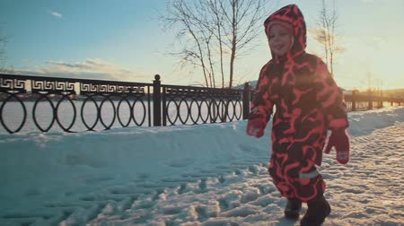 buty : Happy child flees on the paths in the park. A small girl in a pink jumpsuit runs through the snow on a clear sunny evening at sunset, slow motion.
